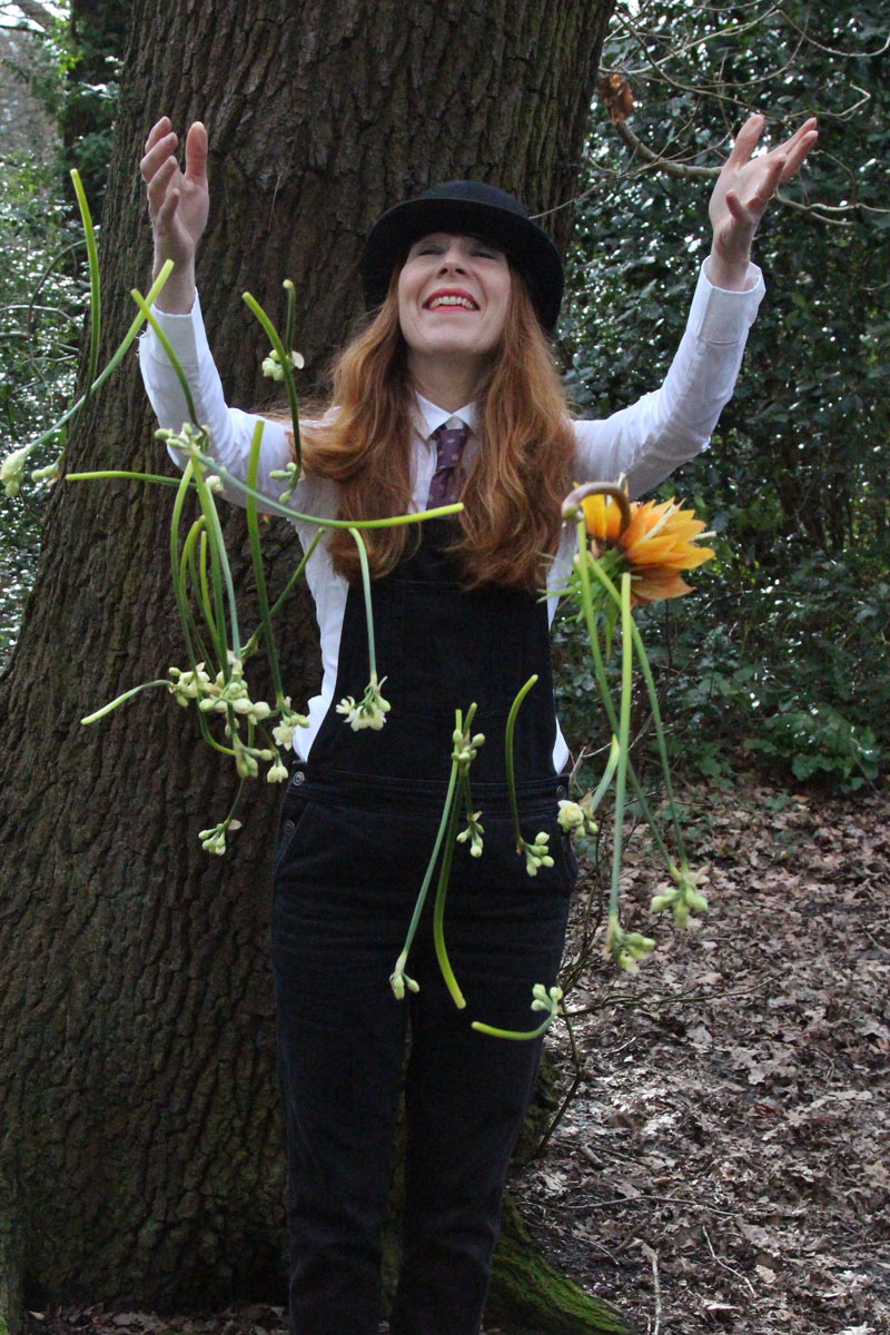 Picture of the author, Rebecca Mays, in a theatre costume throwing flowers in the air.