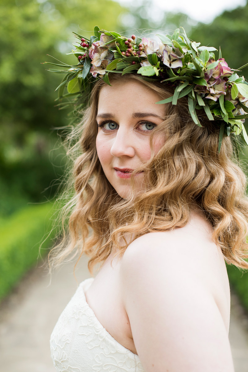 Portrait photograph of a woman wearing a bridal outfit standing in a garden. Her head is dressed with a floral wreath