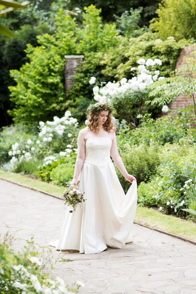 A woman in a bridal outfit walking through a garden in summer