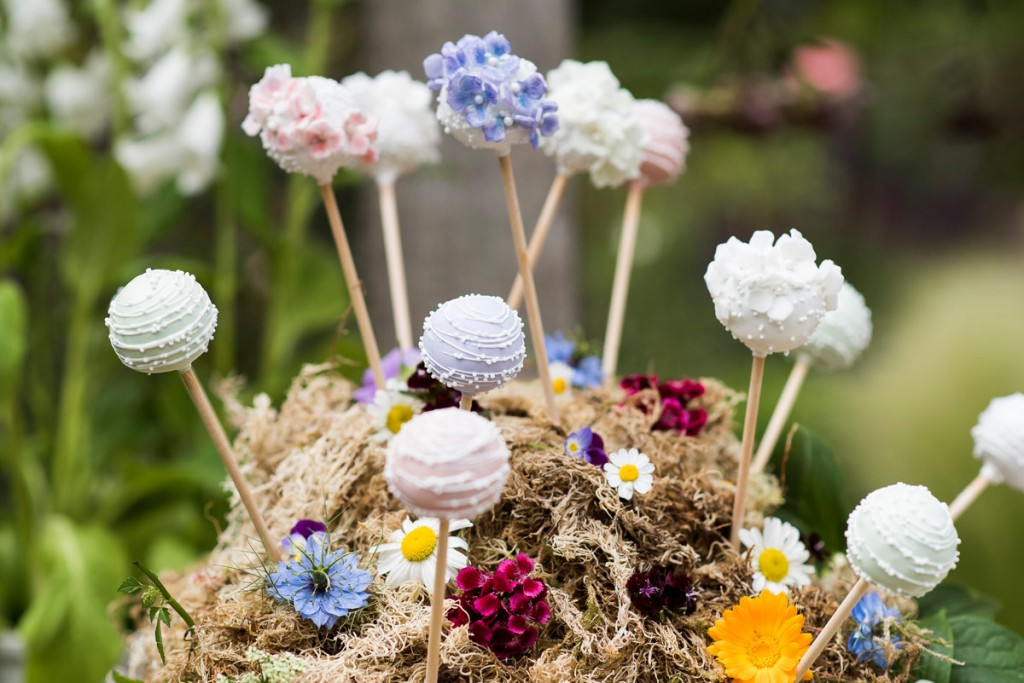 Cake pops and flowers arranged in a mound-shaped support of moss