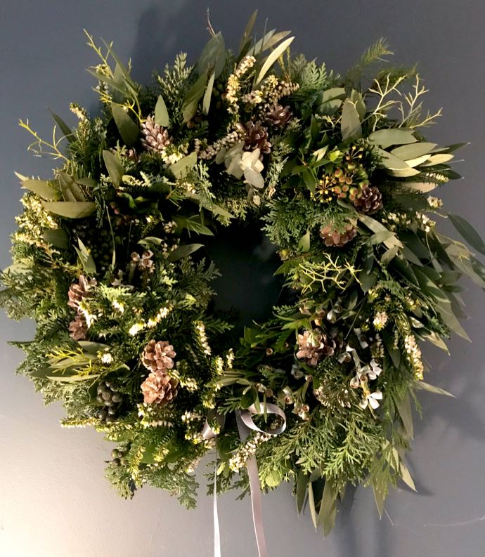 Door wreath featuring evergreen foliage and pine cones